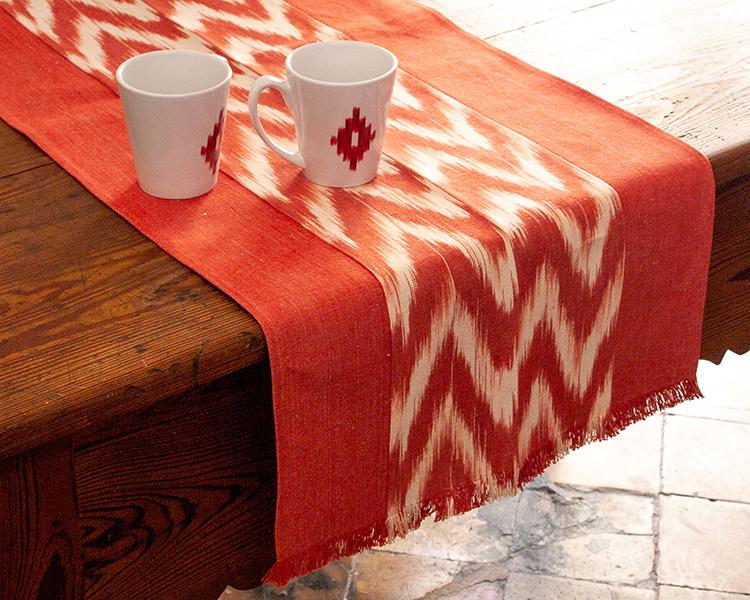 Camino de mesa hecho de ikat o tela mallorquina de color rojo zig zag
